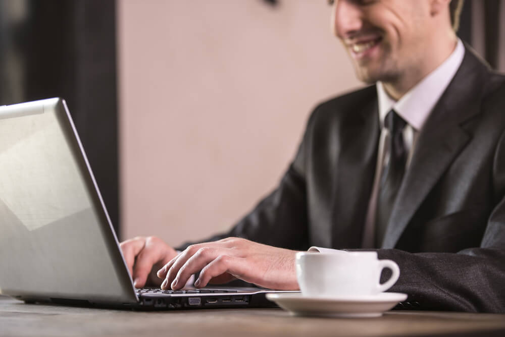 Image of businessman using laptop in cafe